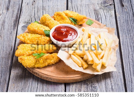 chicken strips and French fries  on rustic wooden background #585351110