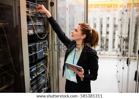 Technician holding digital tablet while examining server in server room Royalty-Free Stock Photo #585381311