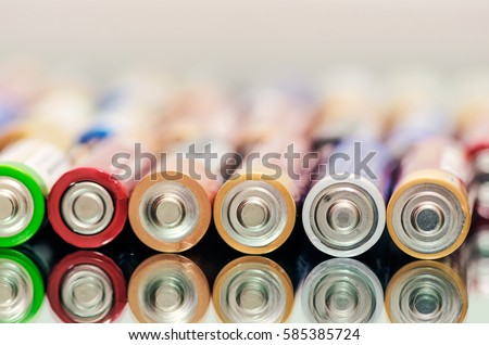 Closeup of pile of used alkaline batteries. Close up colorful rows of selection of AA batteries energy abstract background of colorful batteries. Alkaline battery aa size. Several batteries in rows. #585385724