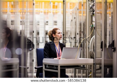 Technician using laptop while analyzing server in server room Royalty-Free Stock Photo #585386138