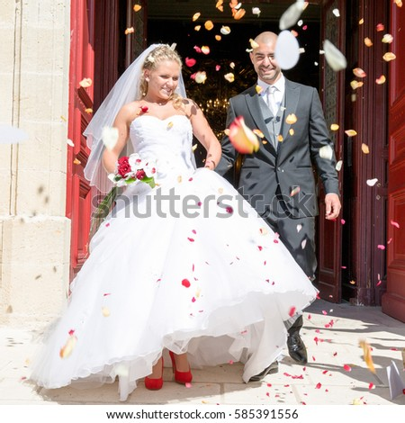 Just married couple under a rain of rose petals #585391556