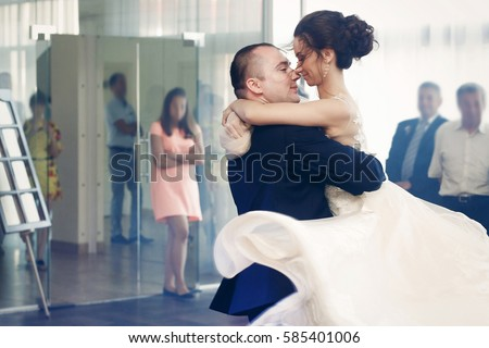 Happy newlywed couple holding hands and dancing at evening wedding reception in luxury dance hall, romance first dance concept #585401006