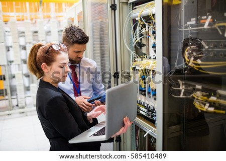 Technicians using laptop while analyzing server in server room Royalty-Free Stock Photo #585410489