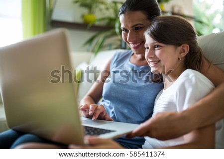 Mother and daughter using laptop and digital tablet in the living room at home #585411374