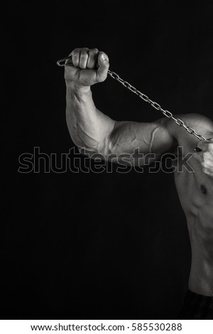 Bodybuilder posing in different poses demonstrating their muscles. Failure on a dark background. Male showing muscles straining. Beautiful muscular body athlete. #585530288
