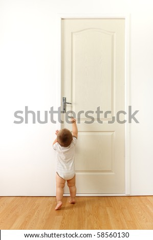 Baby in front of a closed door, trying to reach the keyhole with key #58560130