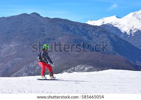 Snowboarder is riding on piste ski #585665054