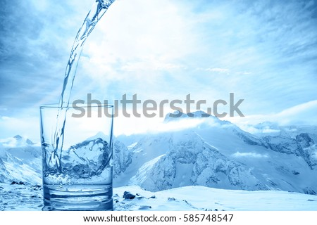 concept purity of blue water in transparent glass over winter landscape of mountains higher than clouds, close up #585748547