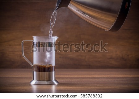 Pouring the hot water into the french press glass  #585768302