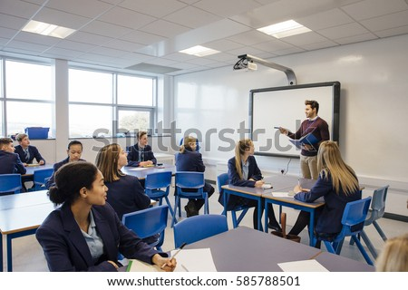 Male teacher is teaching a group of teenagers in a high school lesson. #585788501