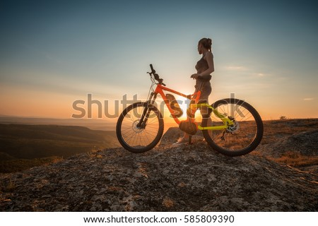 Active life / A woman with a bike enjoys the view of sunset over an autumn forest Royalty-Free Stock Photo #585809390