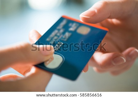 Closeup shot of a woman passing a payment credit card to the seller. Girl holding a credit card. Shallow depth of field with focus on the credit card. #585856616
