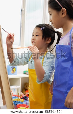 Two girls painting on easel #585914324