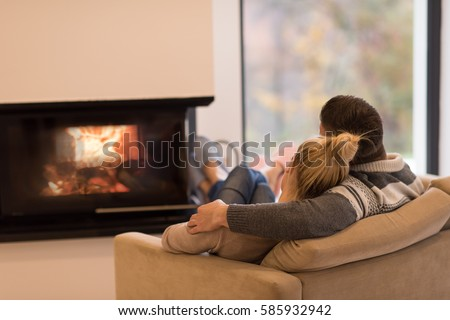 Young romantic couple sitting on sofa in front of fireplace at home, looking at each other, talking and drinking coffee at autumn day #585932942