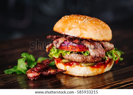 Burger with bacon, meat, tomato and lettuce   on wooden background. Close up #585933215