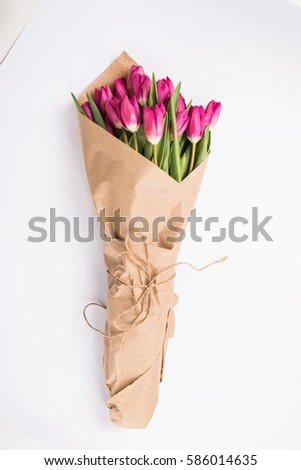 Pink tulips in a package of craft on the white background. Pink tulip. Tulips. Flowers. Flower background. Flowers photo concept. Holidays photo concept. Copyspace #586014635
