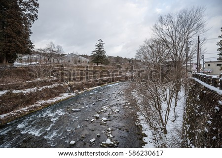 canal waterway in the winter with snowfall in Nikko Japan and the village alongside  #586230617