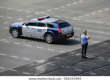 Minsk, Belarus - August 10, 2015: Road police officer salutes a foreign country high authority delegation visiting Belarus #586243484