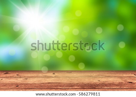 empty wooden table in front of blurred nature background, sunshine in springtime, bokeh lights