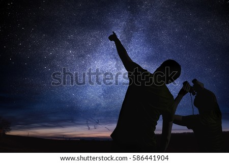Silhouettes of people observing stars in night sky. Astronomy concept. Royalty-Free Stock Photo #586441904