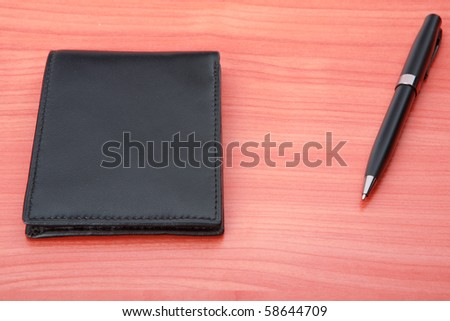 Leather purse lies on a wooden table. Near to purse  pen  lies. #58644709