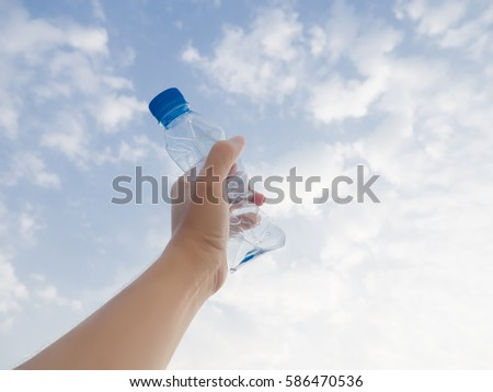 Hand of man holding a plastic empty bottle of water and sky background. #586470536