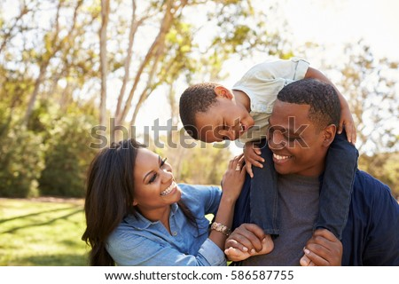 Parents Carrying Son On Shoulders As They Walk In Park Royalty-Free Stock Photo #586587755