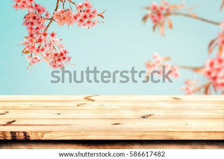 Top of wood table empty ready for your product and food display or montage with pink cherry blossom flower (sakura) on sky background in spring season. vintage color tone.