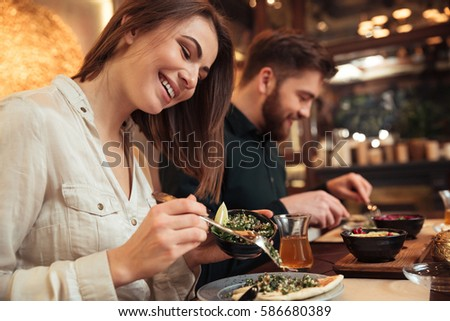 Image of attractive young loving couple sitting in cafe and eating. Looking aside. #586680389