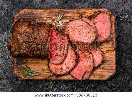 Roast beef on cutting board with salt and pepper. Top view. Royalty-Free Stock Photo #586730513