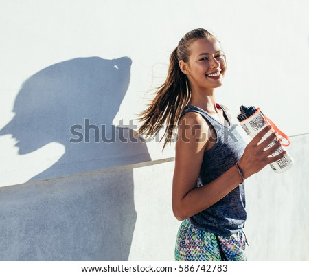 Shot of beautiful female runner standing outdoors holding water bottle. Fitness woman taking a break after running workout. #586742783