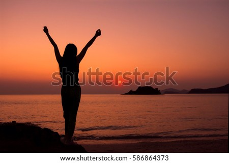 Silhouette of Woman raise arms to celebrate Success or Happiness in Sunrise at Beach, life and power concept #586864373