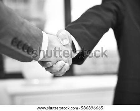 two corporate businessmen shaking hands in office, black and white. #586896665
