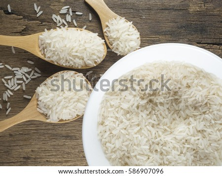 Rice on wooden spoon and bowl on wood background #586907096