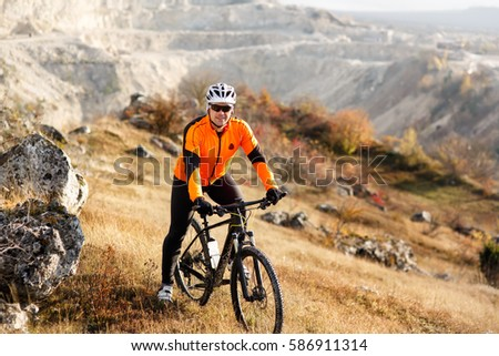 Cyclist Riding the Bike Down Rocky Hill. Extreme Sport Concept. Space for Text. #586911314