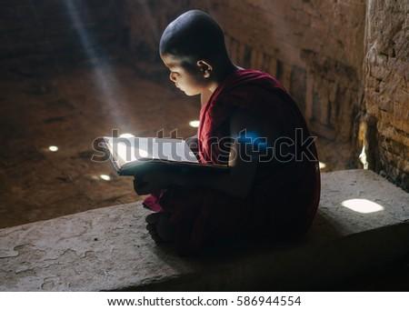 BAGAN, MYANMAR - FEB 03: Little monk reading book in an old pagoda in Bagan, Myanmar on Feb 03, 2017. #586944554