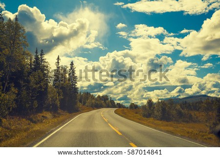Mountain road un sunny day with blue sky and white clouds. Beautiful nature. #587014841