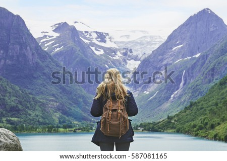 Adventure backpacking woman enjoying view of majestic mountain lake explore travel discover beautiful earth Royalty-Free Stock Photo #587081165