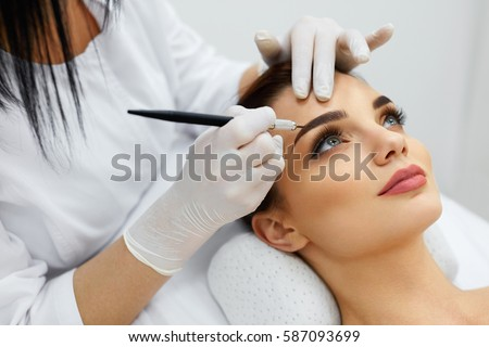 Permanent Makeup For Eyebrows. Closeup Of Beautiful Woman With Thick Brows In Beauty Salon. Beautician Doing Eyebrow Tattooing For Female Face. Beauty Procedure. High Resolution Royalty-Free Stock Photo #587093699