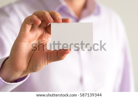 Closeup on businessman holding white empty message card with copy space for text, business concept image with soft focus background #587139344