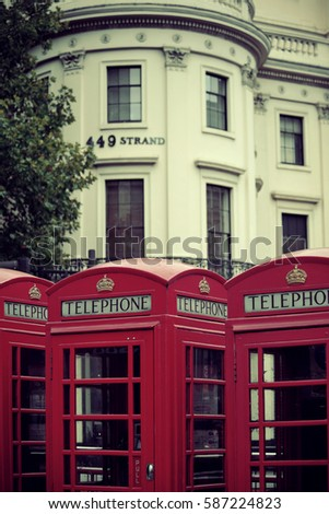 Red telephone box in street with historical architecture in London. #587224823