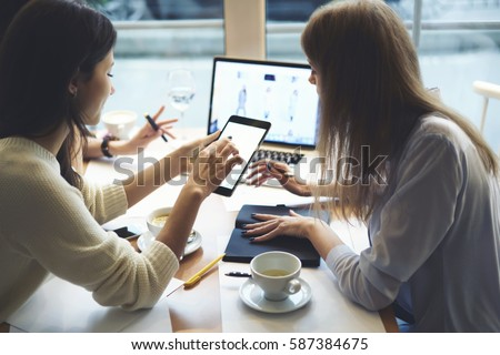 Creative female IT developers coding web site collaborating while working on design layout choosing right colors and multimedia on informal meeting in friendly atmosphere in coffee shop using devices #587384675