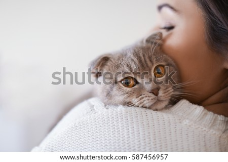 Beautiful young woman with cute cat resting at home #587456957