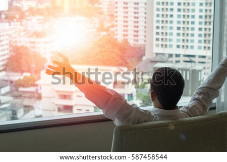 Easy relax business man lifestyle at home sitting on modern chair in living room looking out of window toward beautiful cityscape downtown urban landscape city life w/ sunlight effect: happy people Royalty-Free Stock Photo #587458544