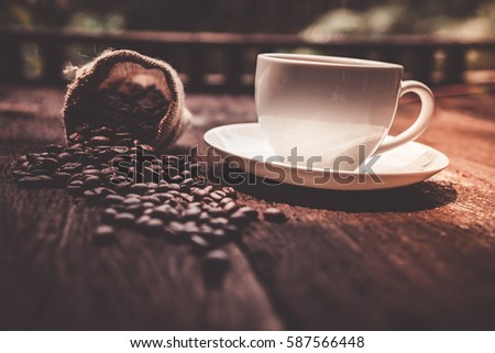 Coffee mug and coffee bean in sack fall on wooden table outdoor background- Vintage effect style pictures
