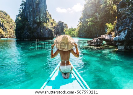 Back view of the young woman in straw hat relaxing on the boat and looking forward into lagoon. Travelling tour in Asia: El Nido, Palawan, Philippines. Royalty-Free Stock Photo #587590211