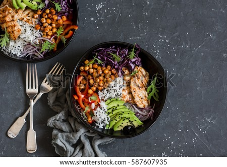 Grilled chicken, rice, spicy chickpeas, avocado, cabbage, pepper buddha bowl on dark background, top view. Delicious balanced food concept     #587607935