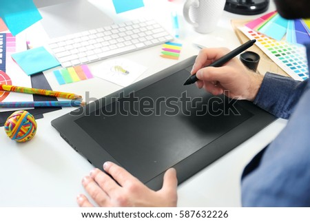 Modern designer working with graphic tablet #587632226