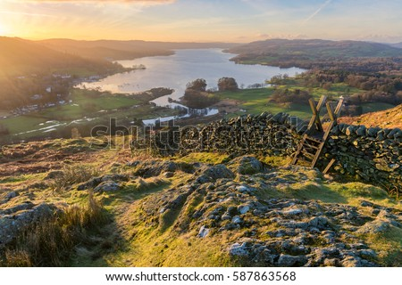 Lake Windermere in the English Lake District taken at sunrise with vibrant colours and golden morning light. Royalty-Free Stock Photo #587863568