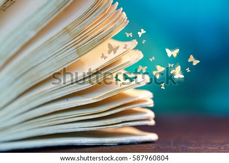 Open pages old magic book on a wooden table close-up macro and departing from the pages of paper butterflies on a blue background. Romantic dreamy artistic image of a fairytale. #587960804